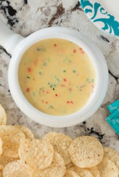 Overhead picture of Warm Jalapeño White Cheddar Dip in a white bowl with tortilla chips