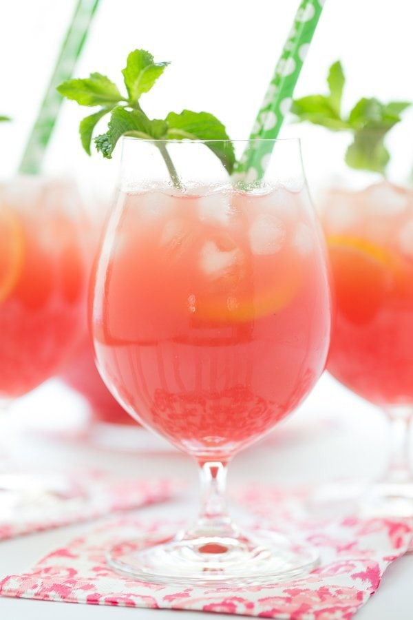 Vertical photo of Watermelon Mint Lemonade in glasses with green straws.