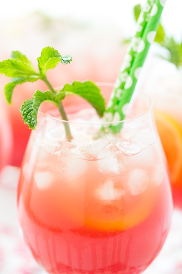 Closeup photo of a glass of Watermelon Mint Lemonade with green straws and a spring of fresh mint.