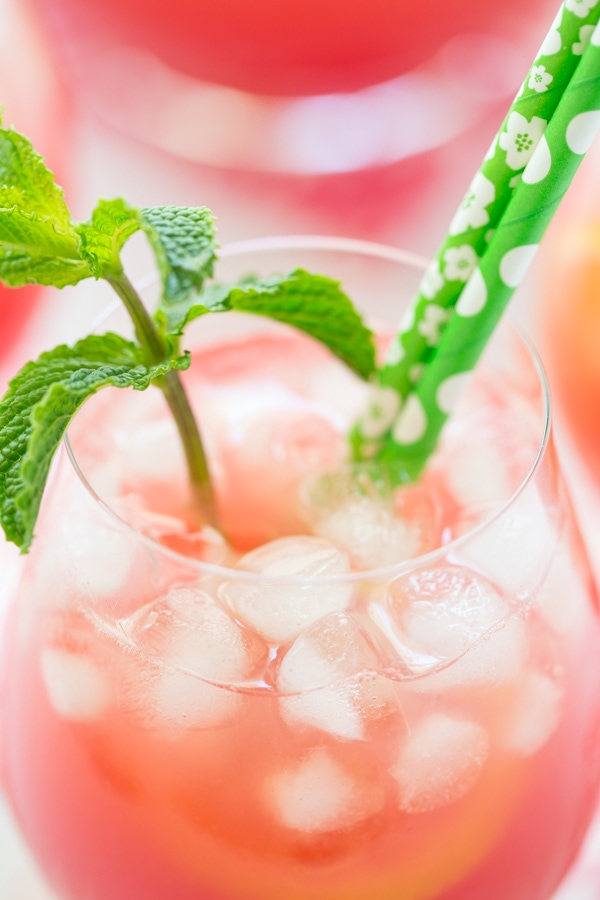 Closeup photo of a glass of Watermelon Mint Lemonade with ice and a sprig of mint.
