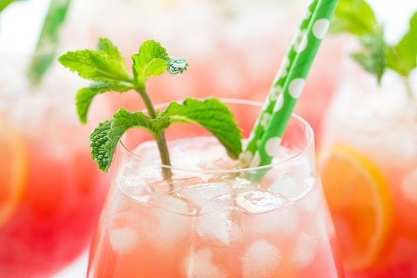 Closeup photo of the top of a glass of Watermelon Mint Lemonade surrounded by other glasses. The drink is decorated with a sprig of mint.