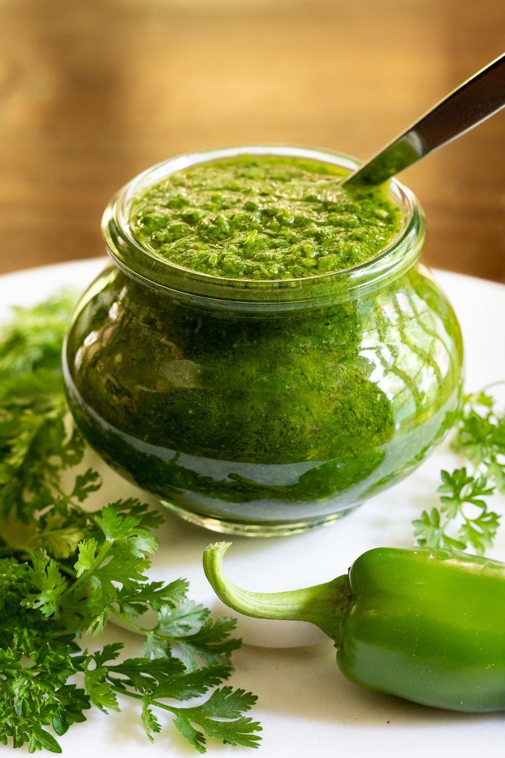Vertical closeup photo of Middle Eastern Zhoug sauce in a glass Weck jar surrounded by cilantro and peppers.