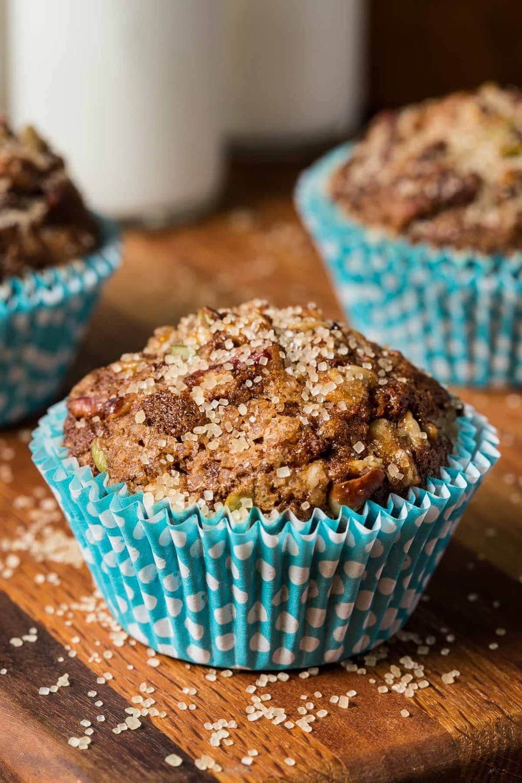 Vertical photo of Zucchini Morning Glory Muffins in turquoise muffin wrapper on a wooden cutting board with glasses of milk in the background.