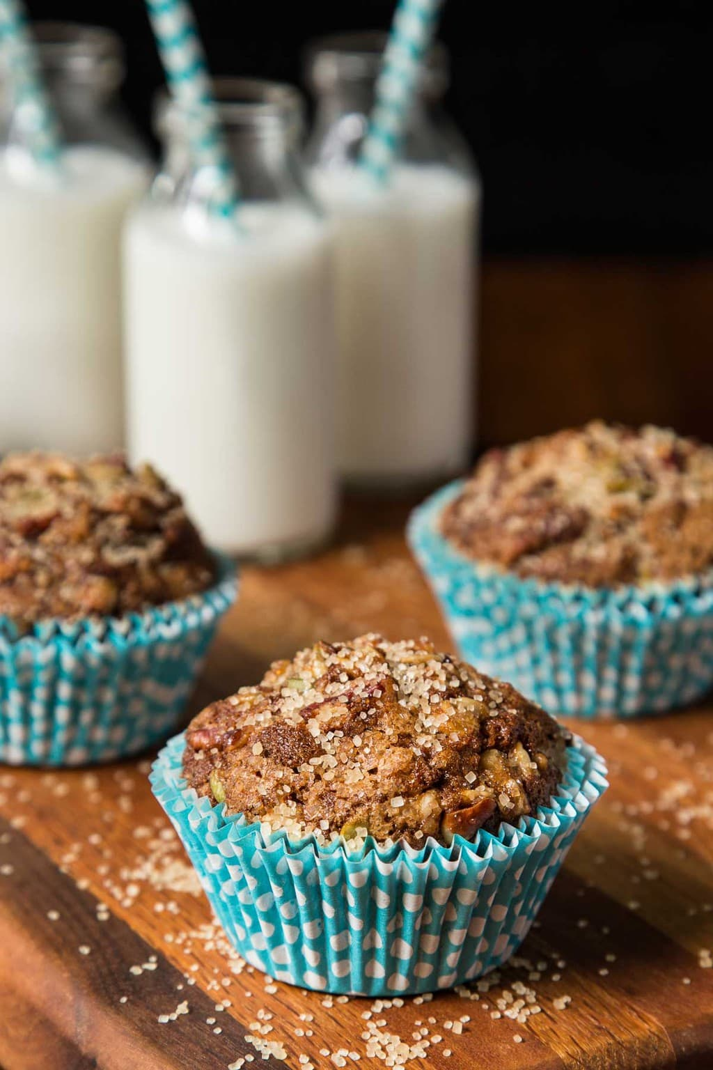 Vertical photo of Zucchini Morning Glory Muffins on a wood cutting board with small bottles of milk in the background.
