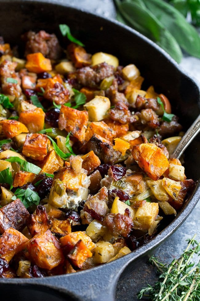 "Photo of a cast iron skillet of Paleo Butternut Sausage Stuffing with Apples & Cranberries from ""19 Delicious Thanksgiving Sides"" blog post."
