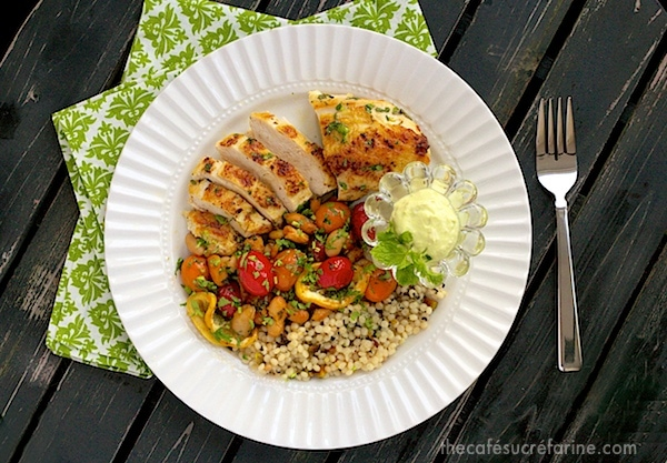 An overhead photo of a dish of Mediterranean Roasted Chicken Breasts on a dark wood table with green and white napkins under the white plate.