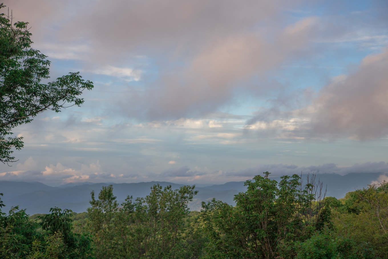 Panoramic shot of the North Carolina Mountains with green trees and a colorful, stormy sky.