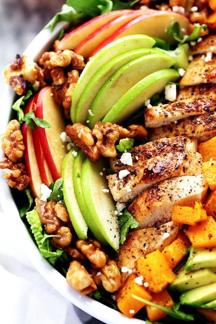 15 Delicious Fall Salads - A photo of a salad with apples, sliced chicken, walnuts, sliced avocado and roasted butternut squash.