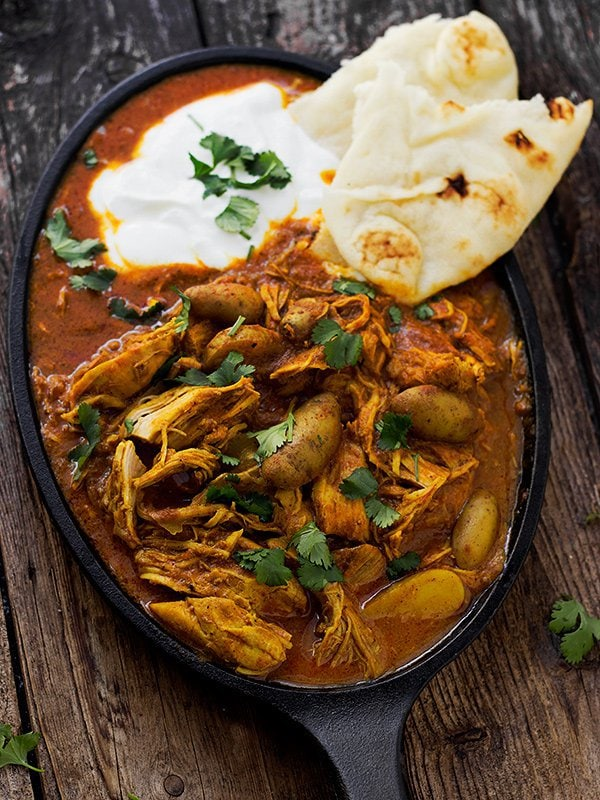 Overhead picture of Indian Spiced Chicken Stew with naan in a cast iron skillet