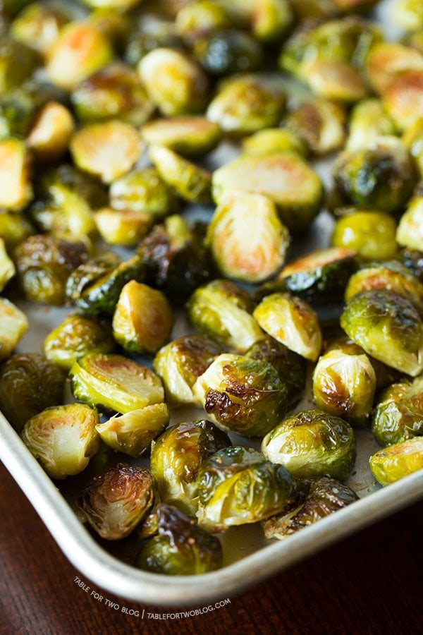 "Photo of a baking sheet of Roasted Garlic Brussels Sprouts from ""19 Delicious Thanksgiving Sides"" blog post."