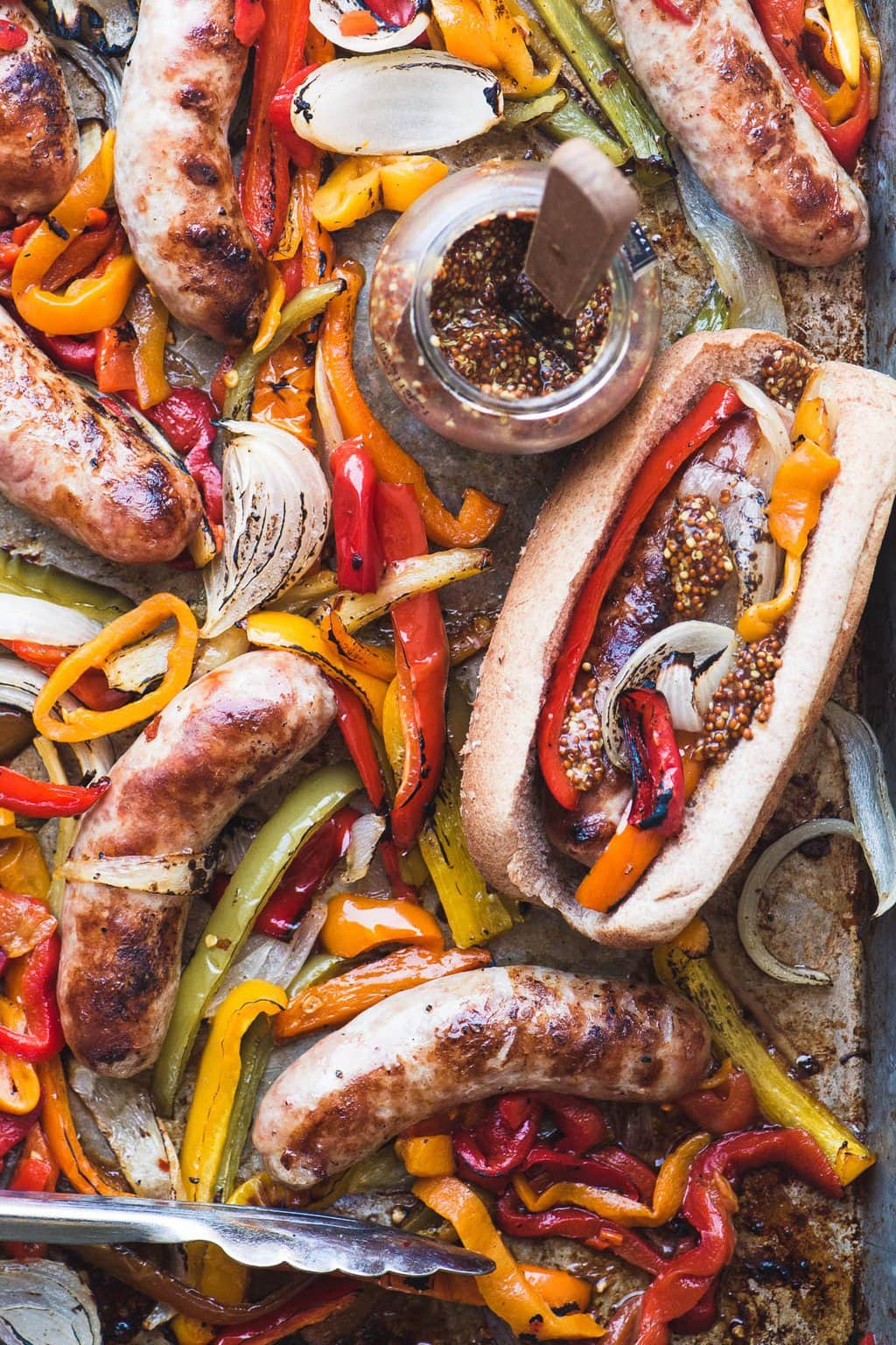 Overhead photo of Sheet Pan Peppers and Brats with a bottle of spices and silver tongs on the pan.